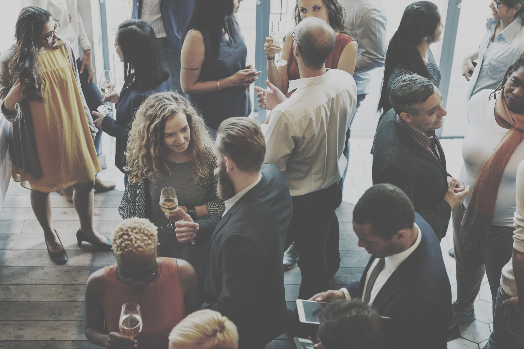 Group of men and women talking in casual cocktail setting forming SB and DBE partnerships