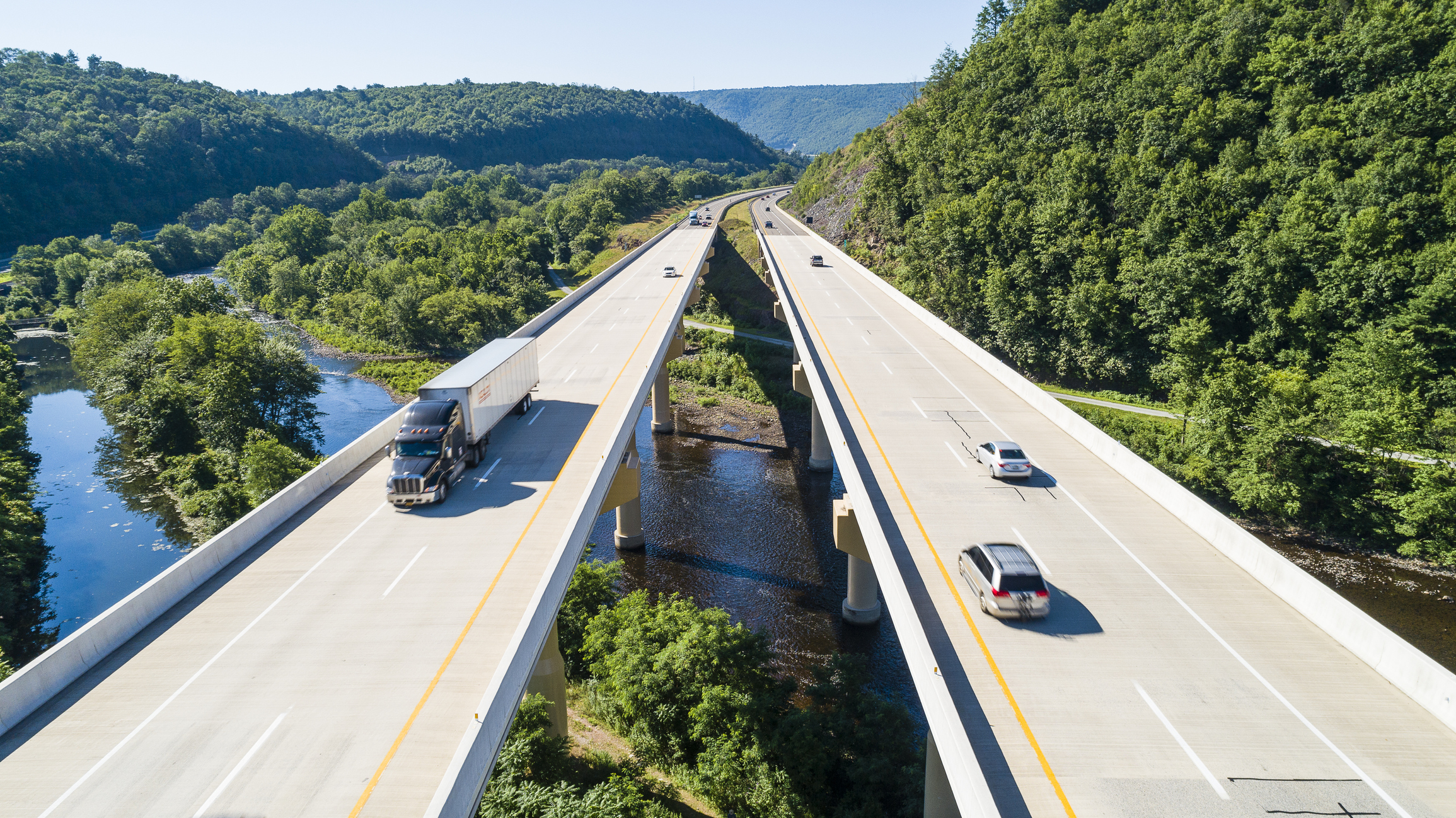 Transportation impacts due to trucks and cars travelling through mountains on bridge spanning river