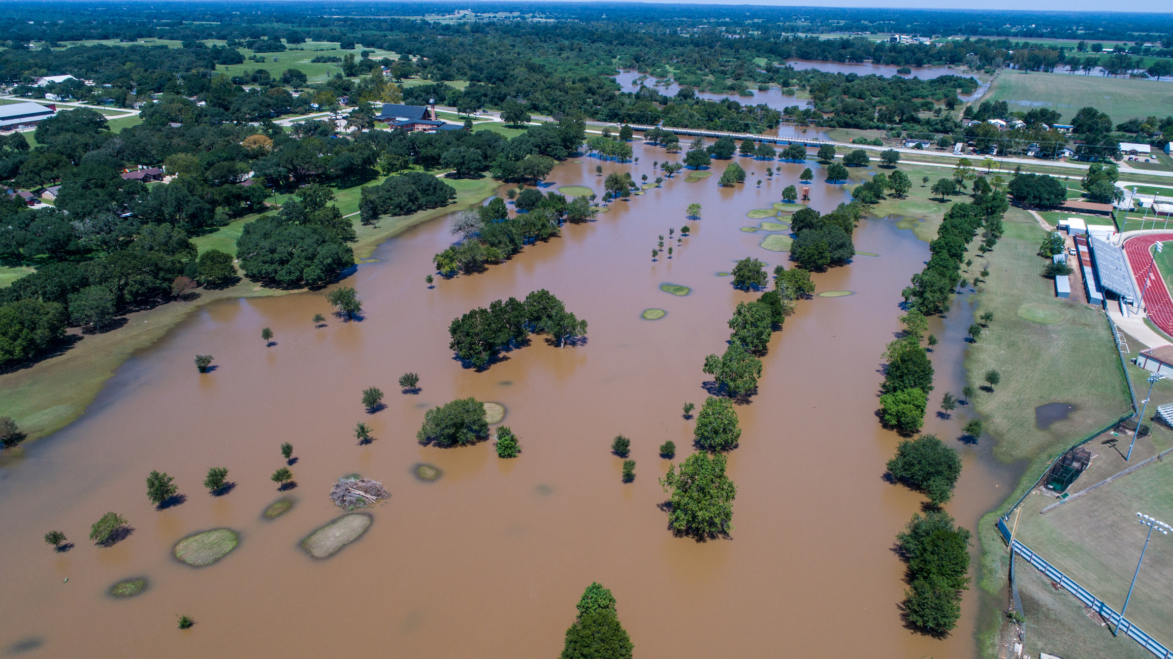 Aerial mapping of natural disaster area showing brown flood water inundating area with a lot of trees