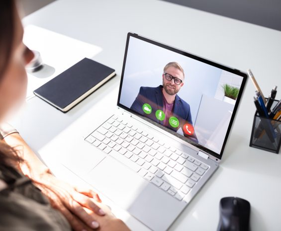 Man watches as woman talks on computer screen.
