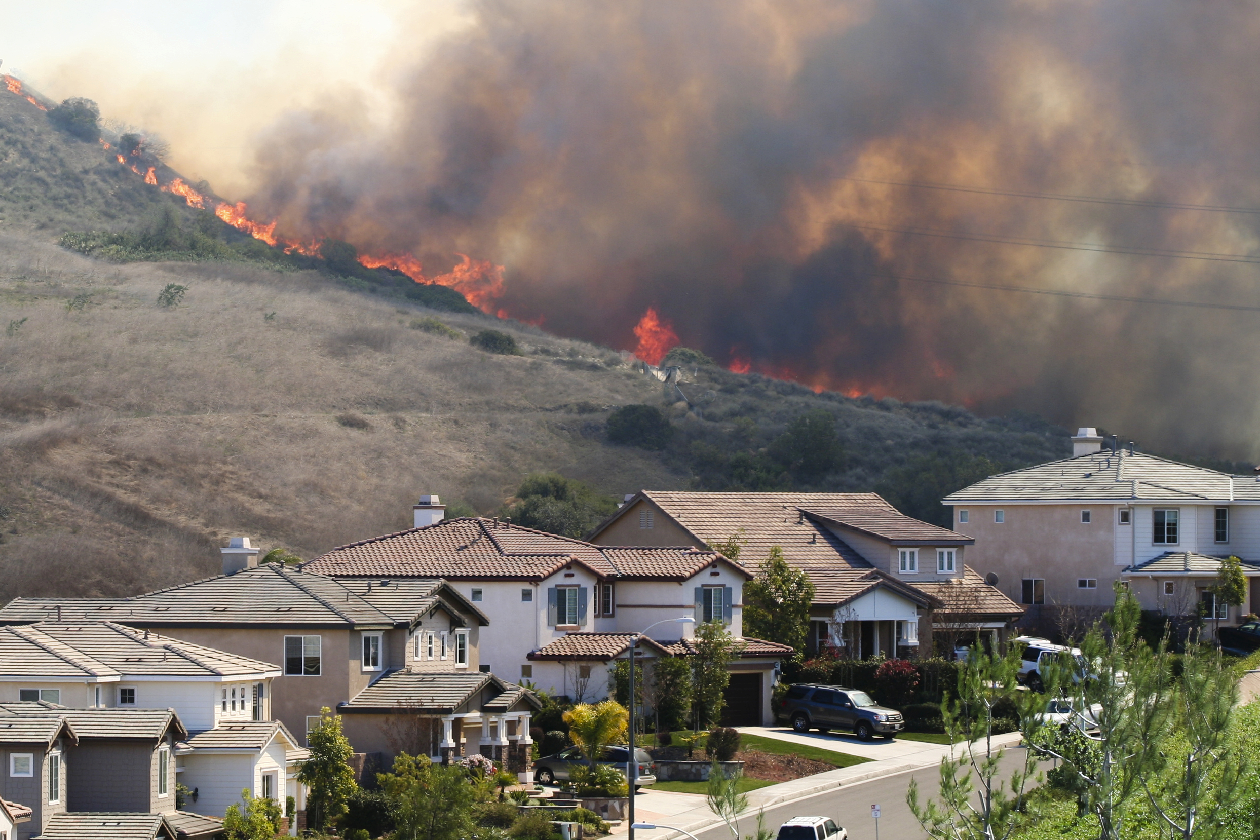 Wildfire burns on hill behind neighborhood homes