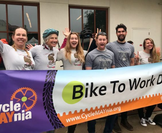 GrDudek staff pose behind Bike to Work Day banner