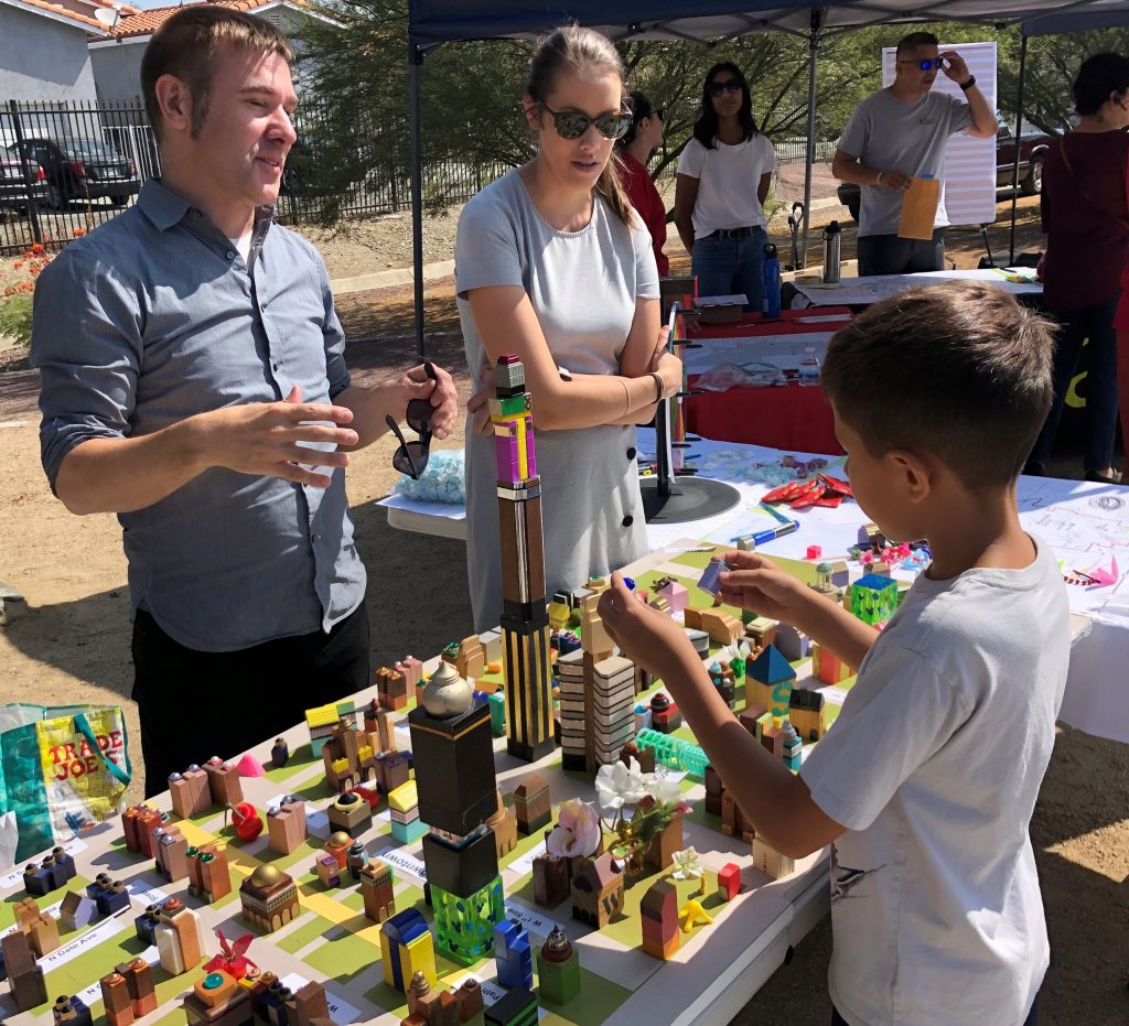 A man and a woman stand behind a table covered with a model of a city, while a child from an environmental justice community stands in front of the table playing with the model.