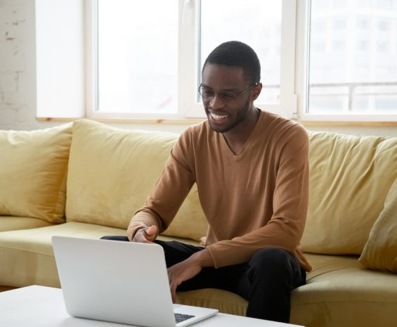 Smiling african american black man sits on couch with laptop open on coffee table in front of him