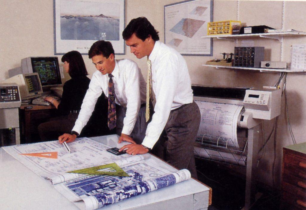 Dudekian Paul Caligiuri poses next to a full-size HP plotter.