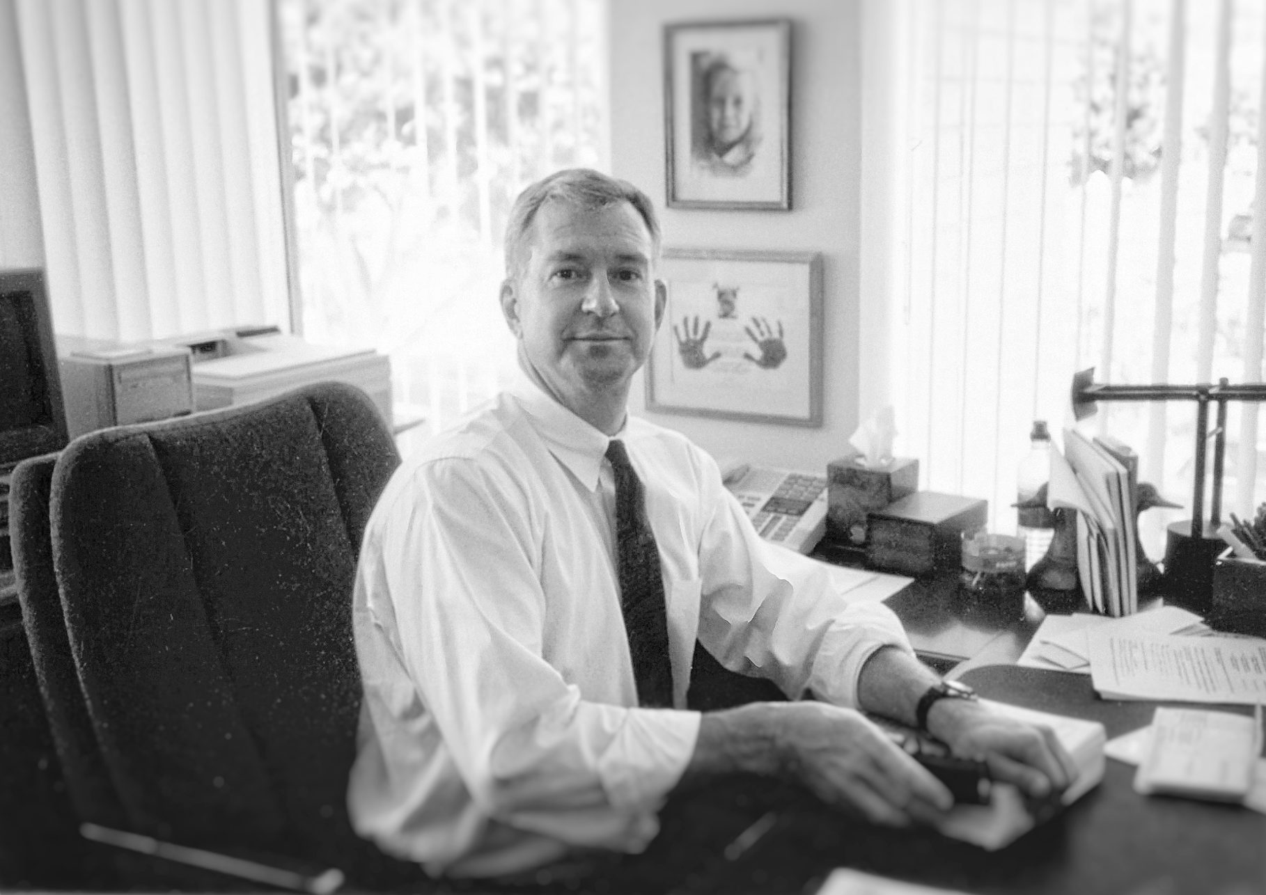 Black and white photo of Frank Dudek, sitting at his desk, looking at the camera.
